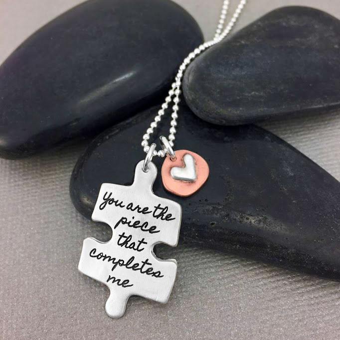 Silver Puzzle necklace with handwritten saying, shown close up
