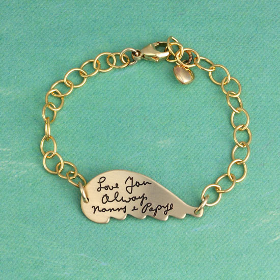 Gold memorial handwriting angel wing bracelet with your loved ones actual handwriting, shown on green