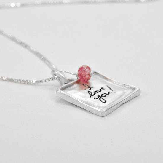 Raised edge handwriting heart necklace, shown from side with pink stone