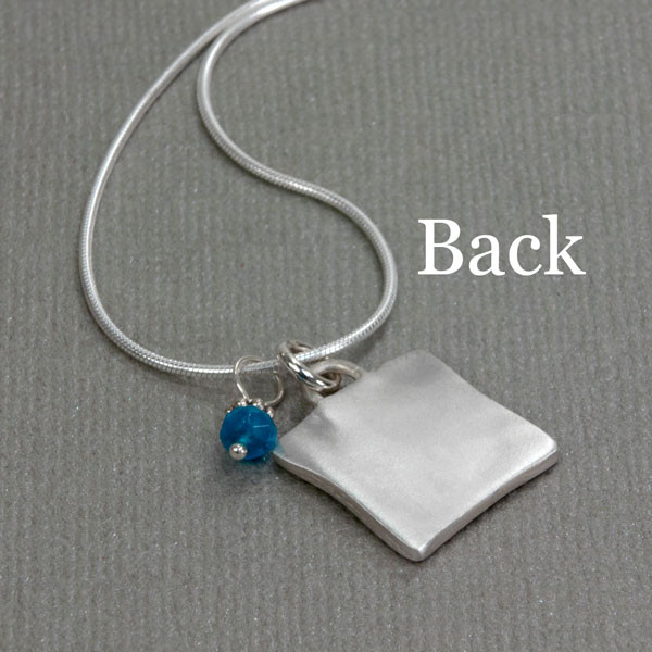 Back side of silver Sculpted Raised Edge Small Square Handwriting Necklace, shown from the side
