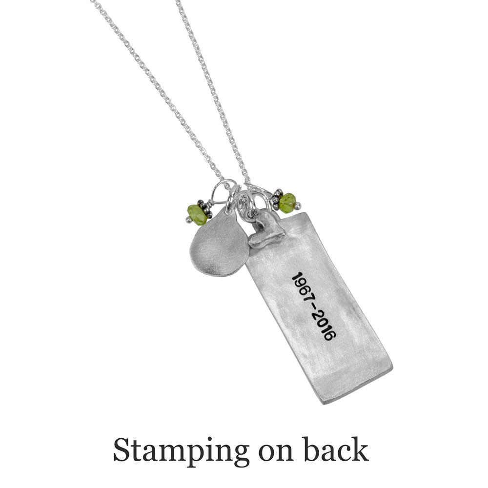 Back side of memorial rectangle family necklace in silver with handwriting, shown with stamped dates on the back