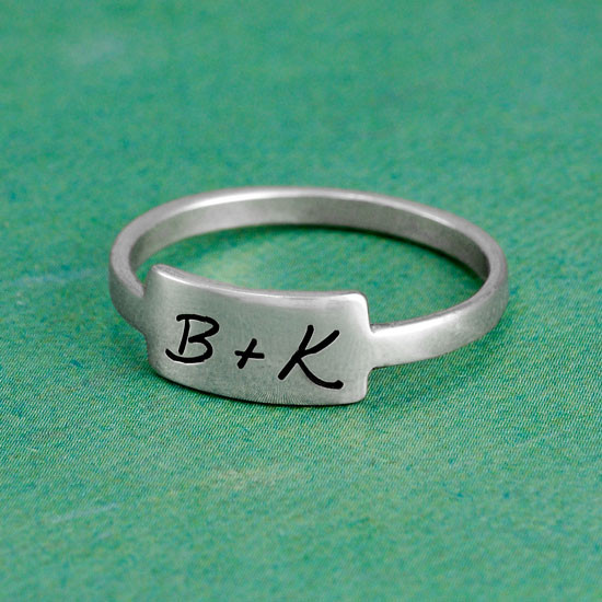 Silver handwritten love note on a ring on green background with B+K on it