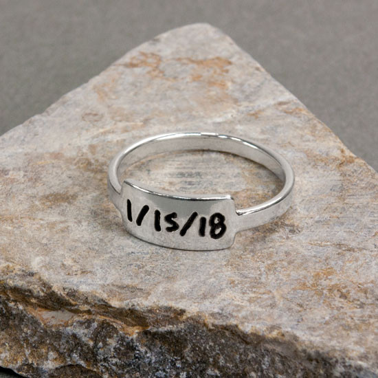 Silver handwriting ring with your handwritten note on stone background