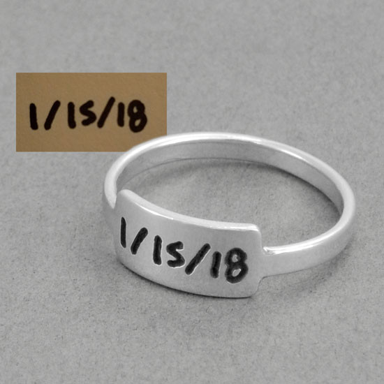 Silver handwriting ring with your handwritten note on gray background shown with original handwriting used to create the ring. a date is engraved on the ring