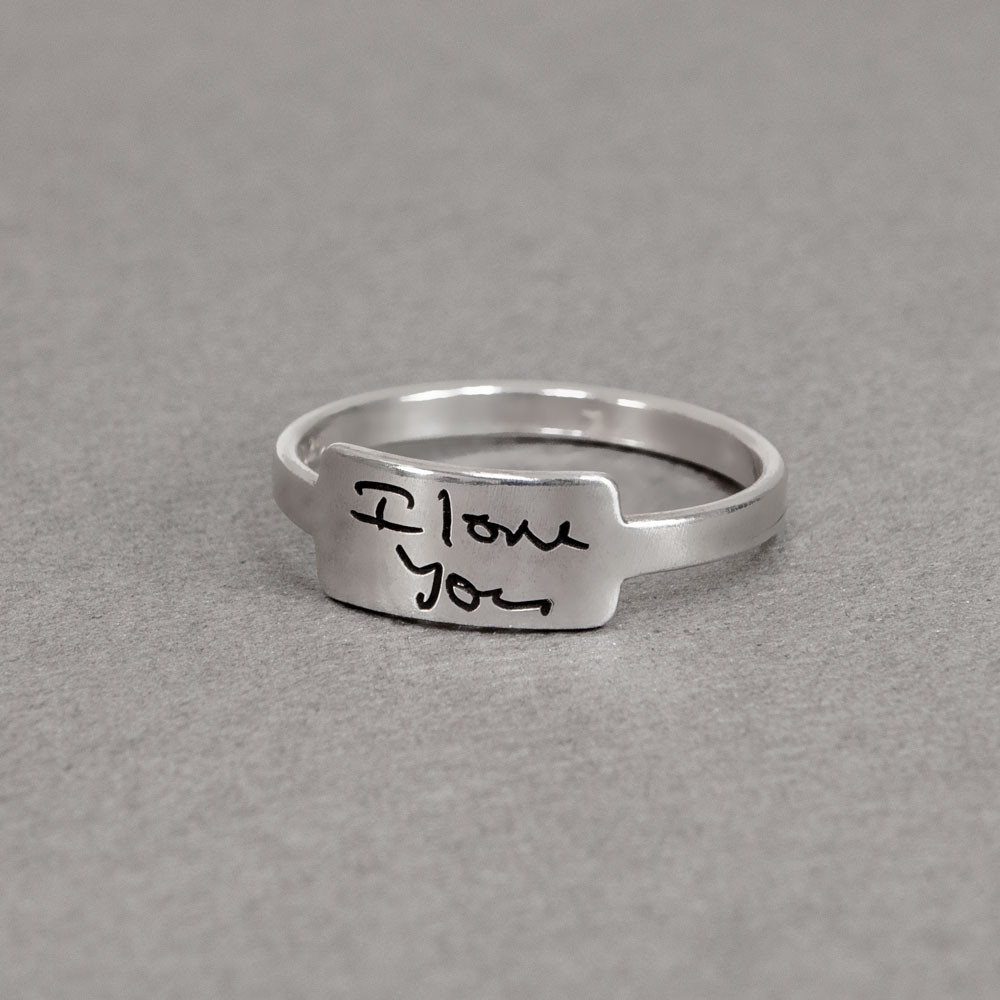 Silver handwriting ring with your handwritten note, shown from the side, on a gray background