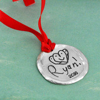 Custom fine pewter Christmas ornament, personalized with your child's artwork, shown close up on green
