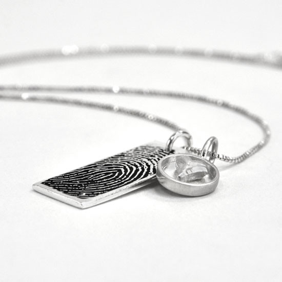 Custom Silver fingerprint necklace, personalized with your loved one's fingerprint, shown from the side with heart charm