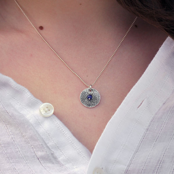 Close up of round sterling silver fingerprint necklace with birthstone on model