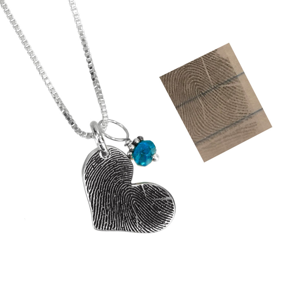 Silver fingerprint heart necklace with birthstone, shown close up on from the side with original fingerprint used to create it