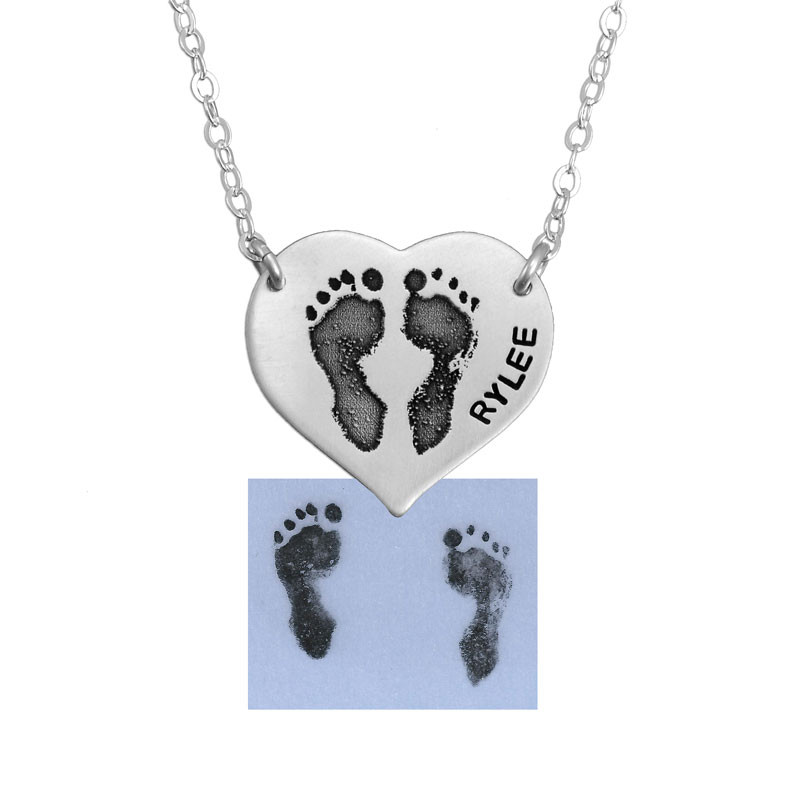 Sterling silver footprint necklace hanging from two holes in charm, shown with actual footprints used to make it