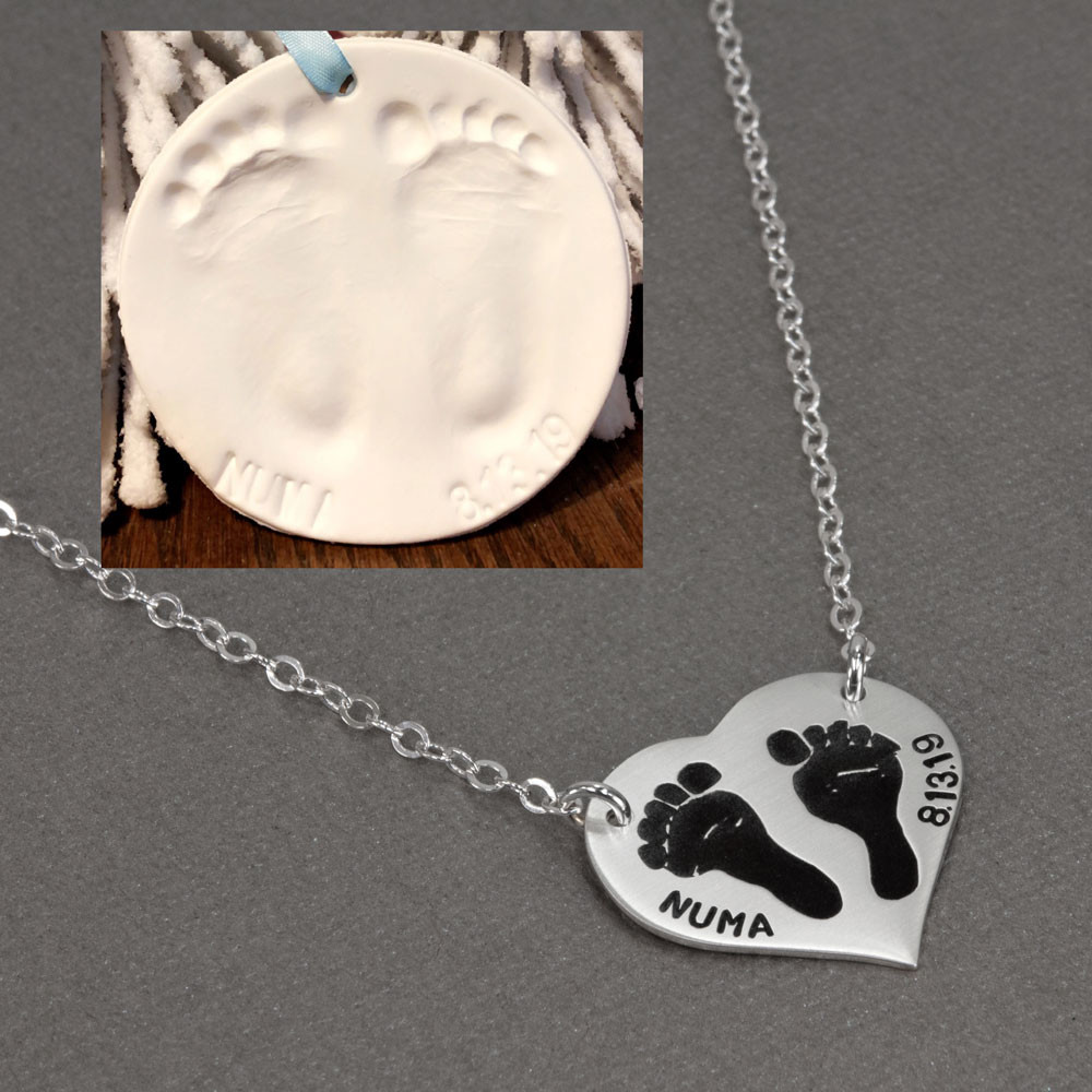 Children's footprints necklace, on a sterling silver heart, with the name hand stamped on the edge of the charm, shown  with plaster cast of original footprints