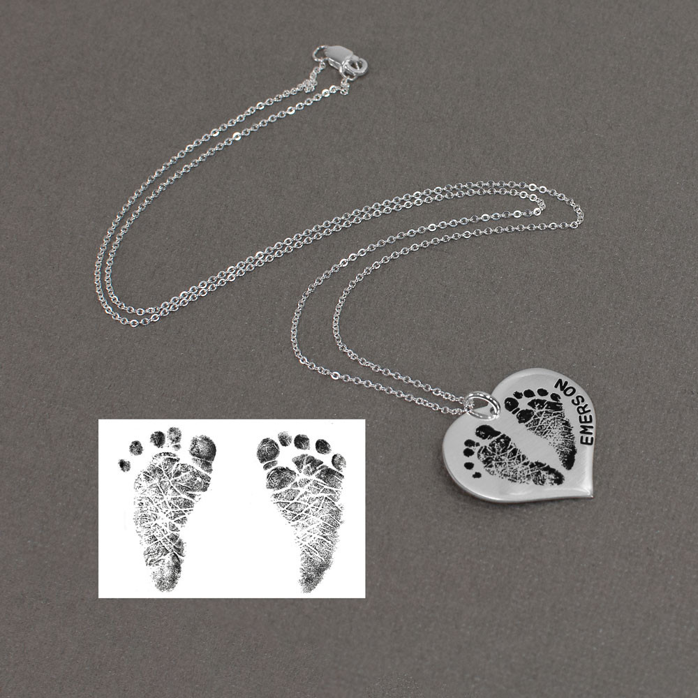 Children's footprints necklace, on a sterling silver heart, with the name hand stamped on the edge of the charm, shown with original footprints