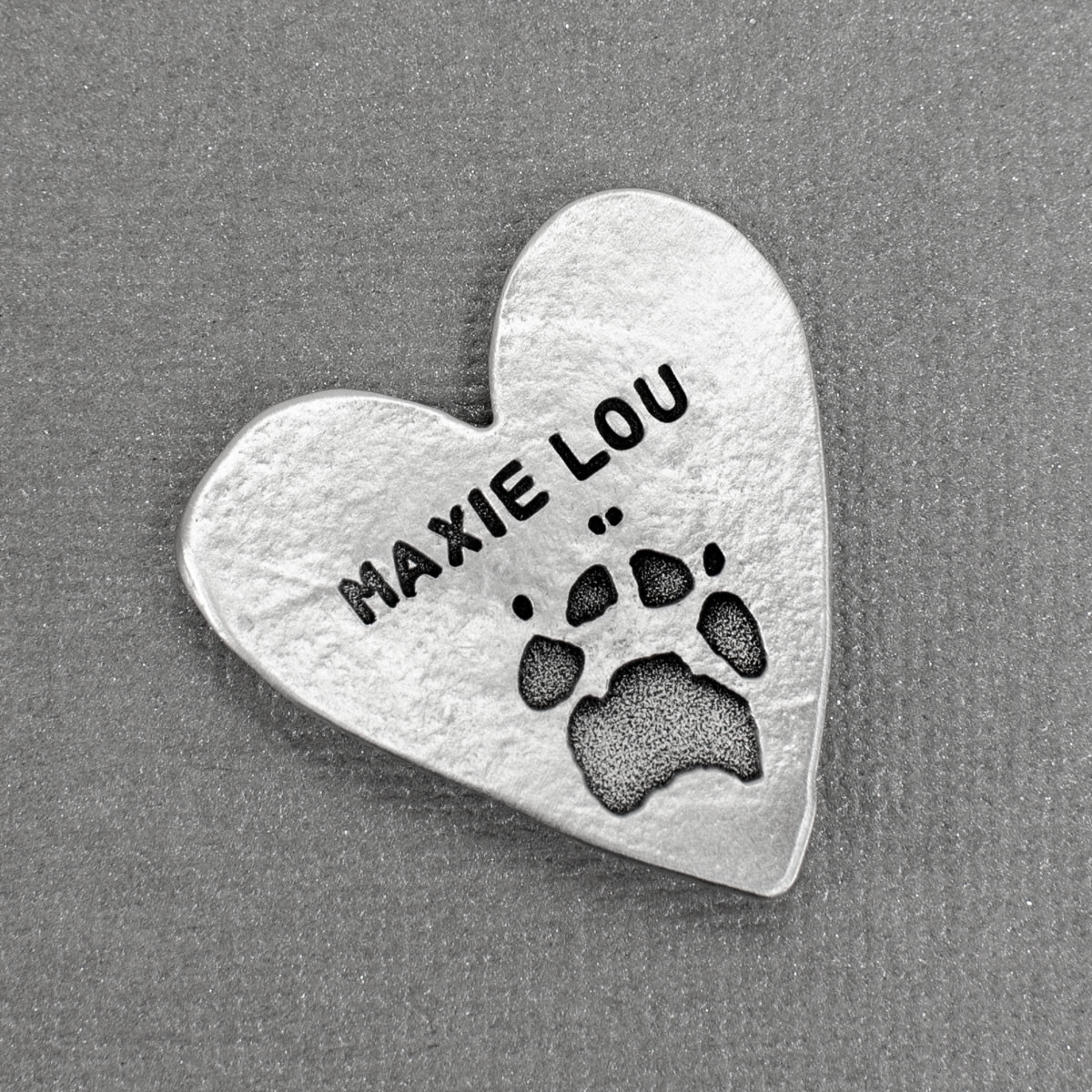 Your pet's paw print etched into a heart pocket token