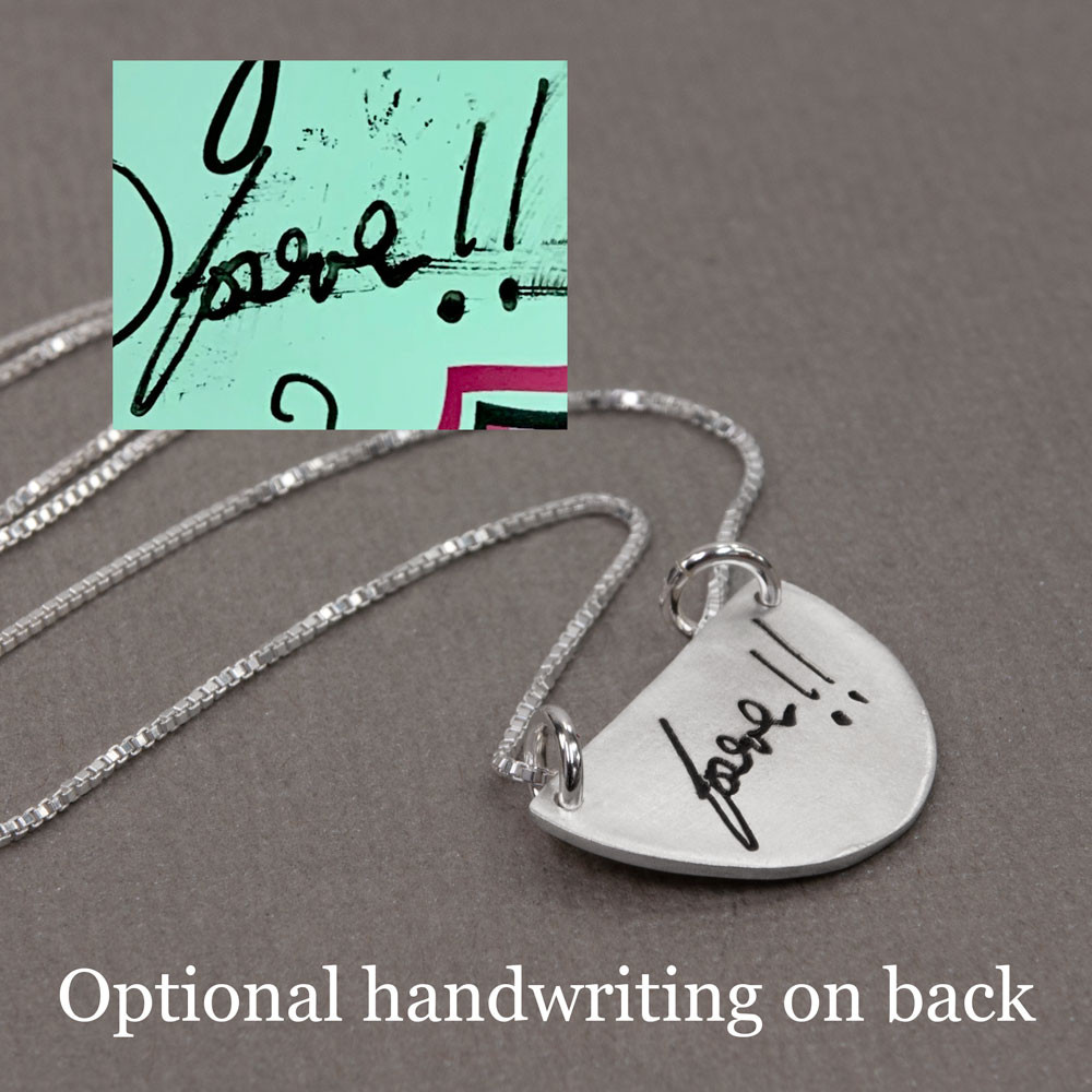 Handwriting on back of custom silver half circle pendant necklace, shown with original handwritten note, on gray