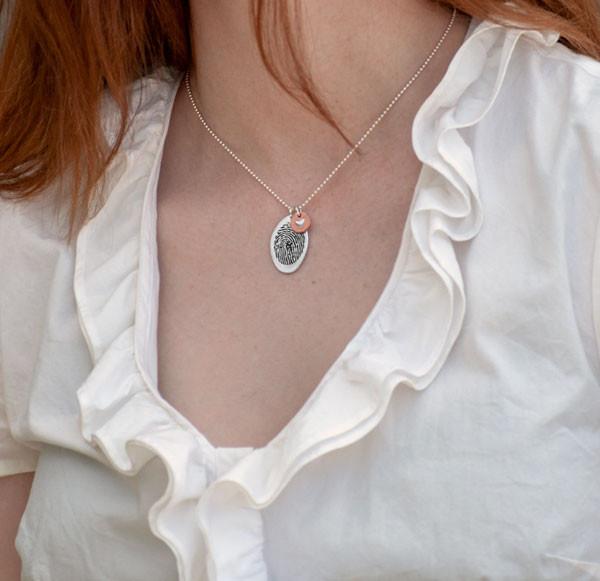 Custom silver fingerprint jewelry with copper heart shown on model