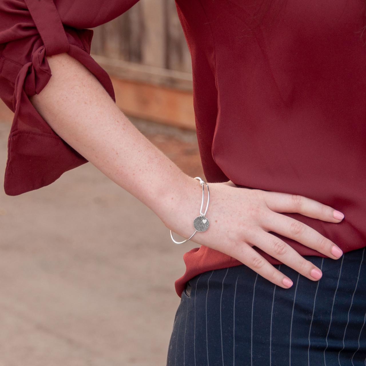Adjustable sterling silver bracelet with custom fingerprint charm, shown on a model