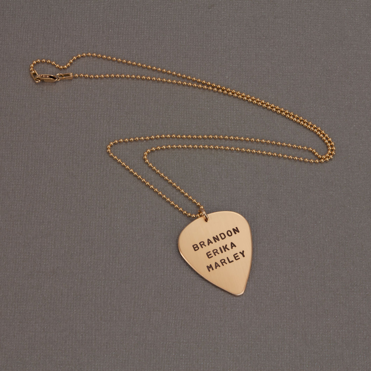 hand stamped personalized guitar pick in gold, shown on  gray