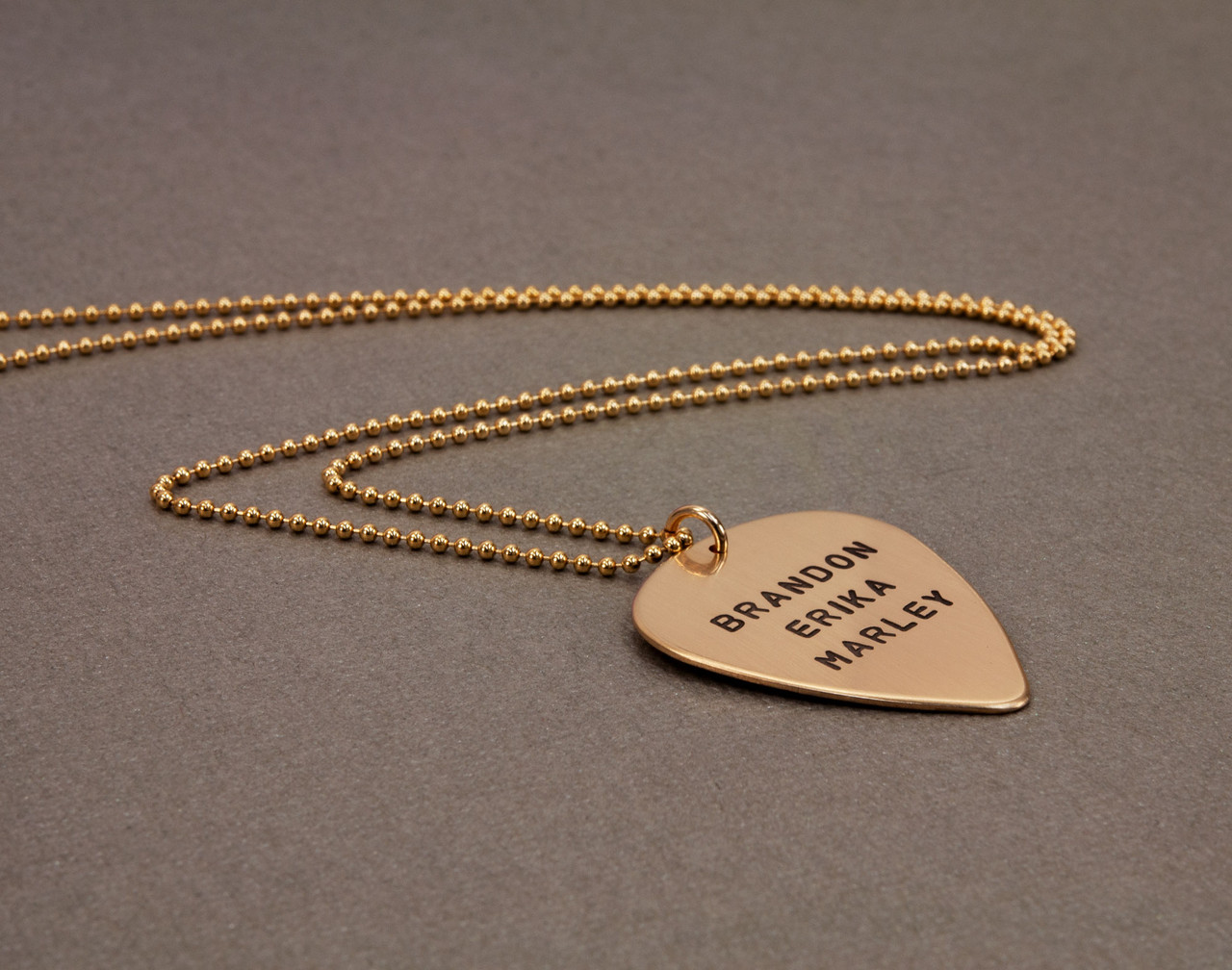 hand stamped personalized guitar pick necklace in gold, shown from the side