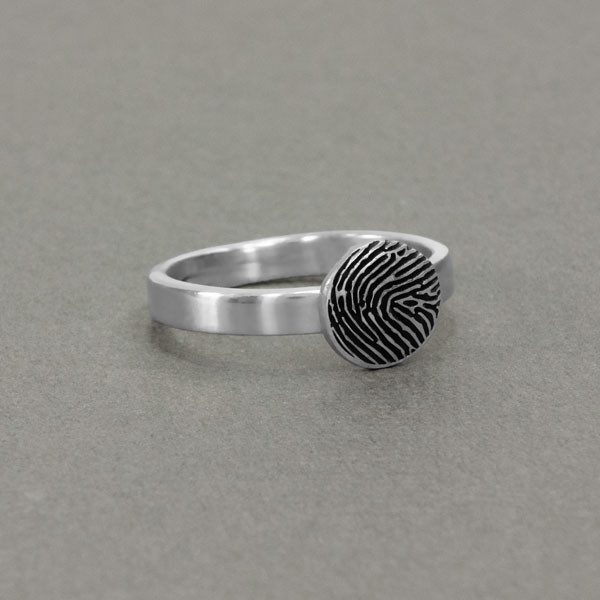 custom circle shaped fingerprint jewelry ring in sterling silver, shown on gray