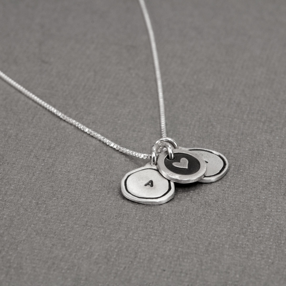 Tiny Framed Initial Charm Necklace made of fine silver, shown from the side