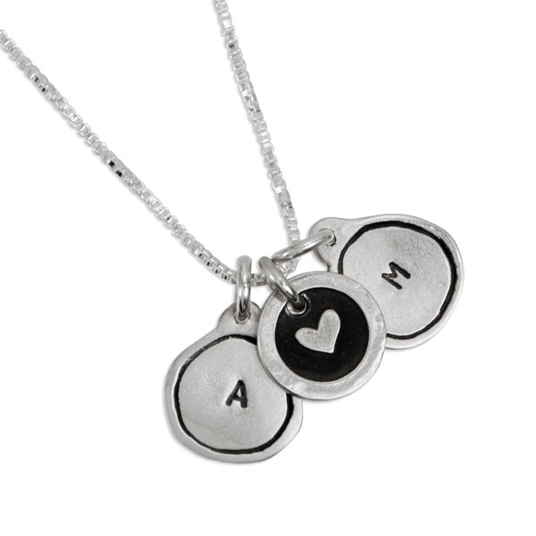 Tiny Framed Initial Charm Necklace made of fine silver, shown on white