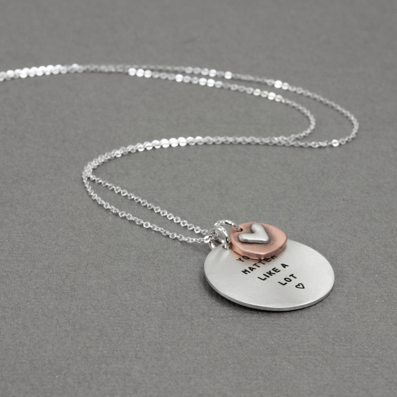 Memorial silver hand stamped necklace shown from the side, with a copper and silver heart
