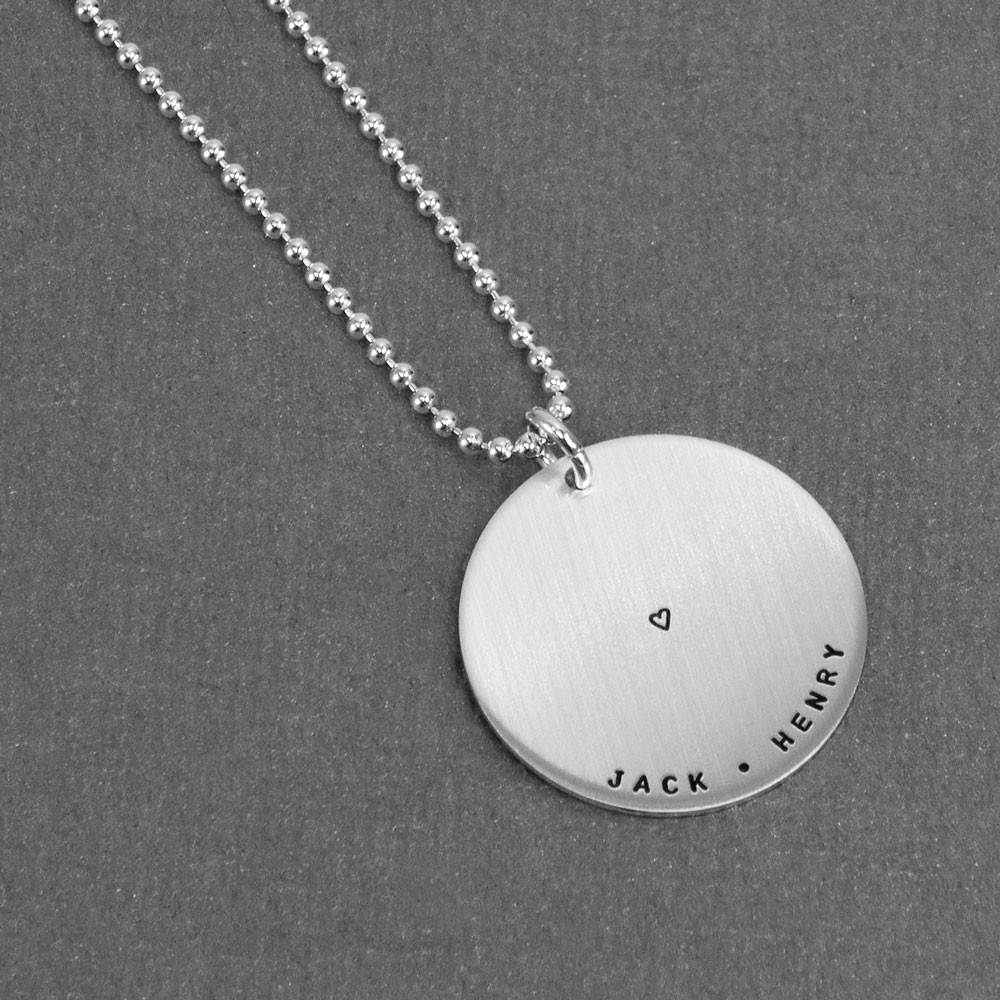 Custom hand stamped silver mother's Love Circle necklace with names in tiny font, shown from the side
