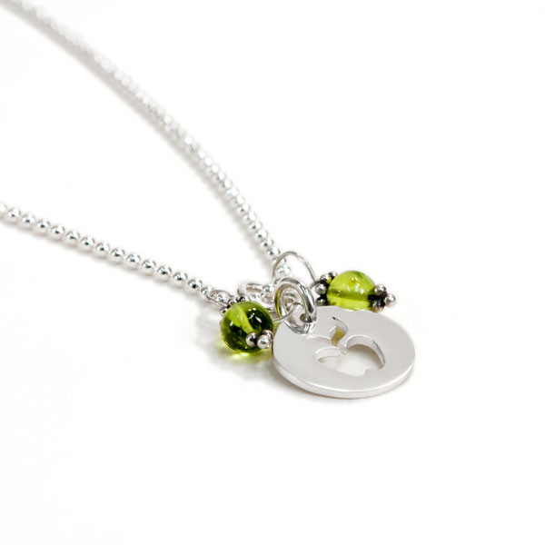 Apple & Peridot Necklace with silver apple teacher gift, from the side on white