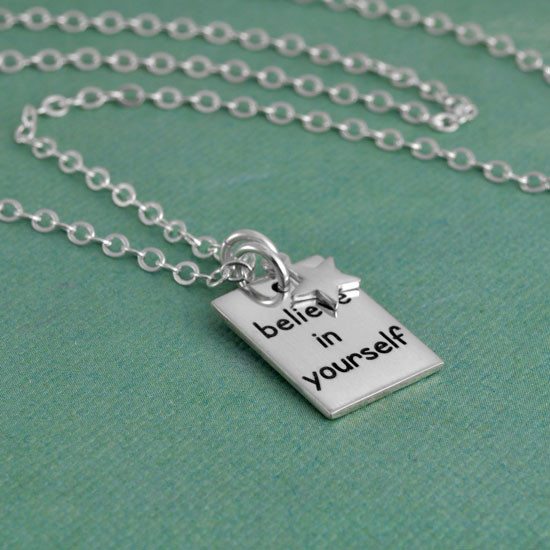 Custom Believe In Yourself Necklace for graduation, hand stamped in sterling silver, with silver star and sterling chain, shown from the side on green background