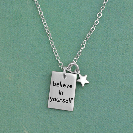 Custom Believe In Yourself Necklace for graduation, hand stamped in sterling silver, with silver star and sterling chain, shown on green background