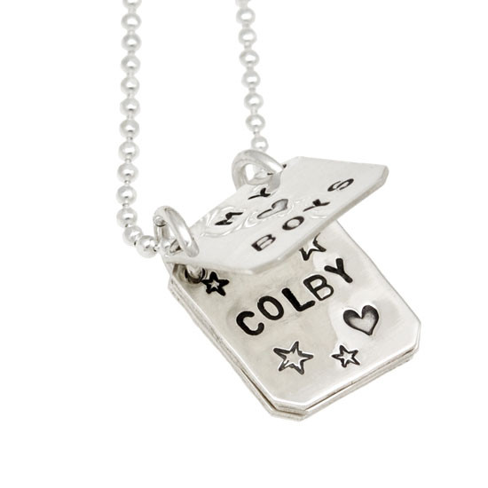 Book Of Love silver hand stamped personalized necklace, shown close up with a page open