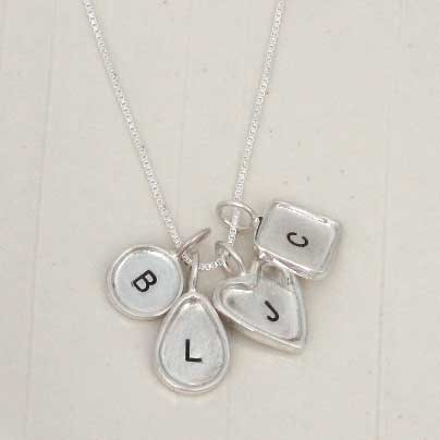 Sterling silver raised edge tear drop and heart raised edge charms, stamped with kids' initials, on a necklace, shown close up on white