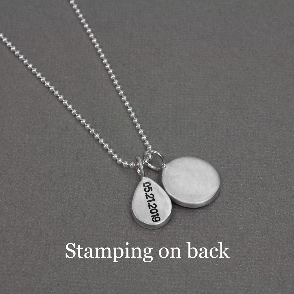 Sterling silver hand stamped raised edge tear drop charm, shown with stamped date on the back