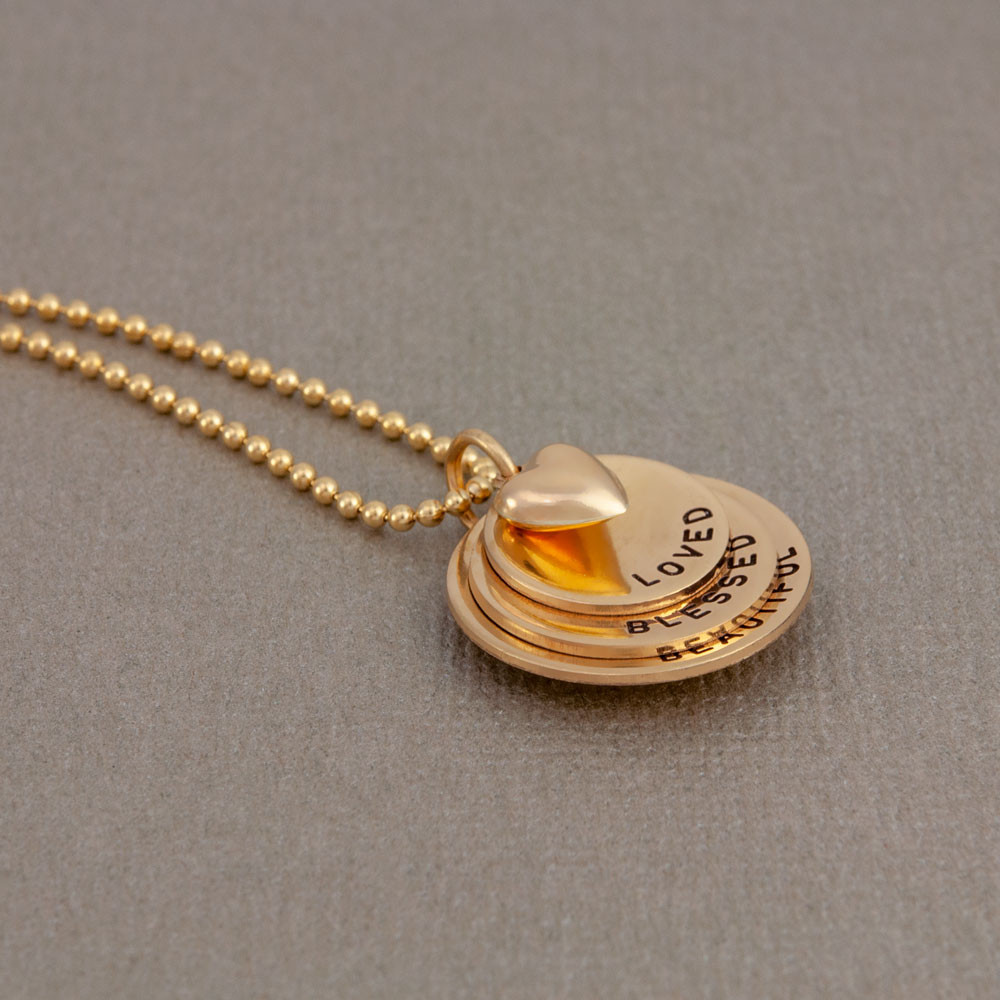 Gold curved discs with heart, stamped with inspirational words, shown from the side
