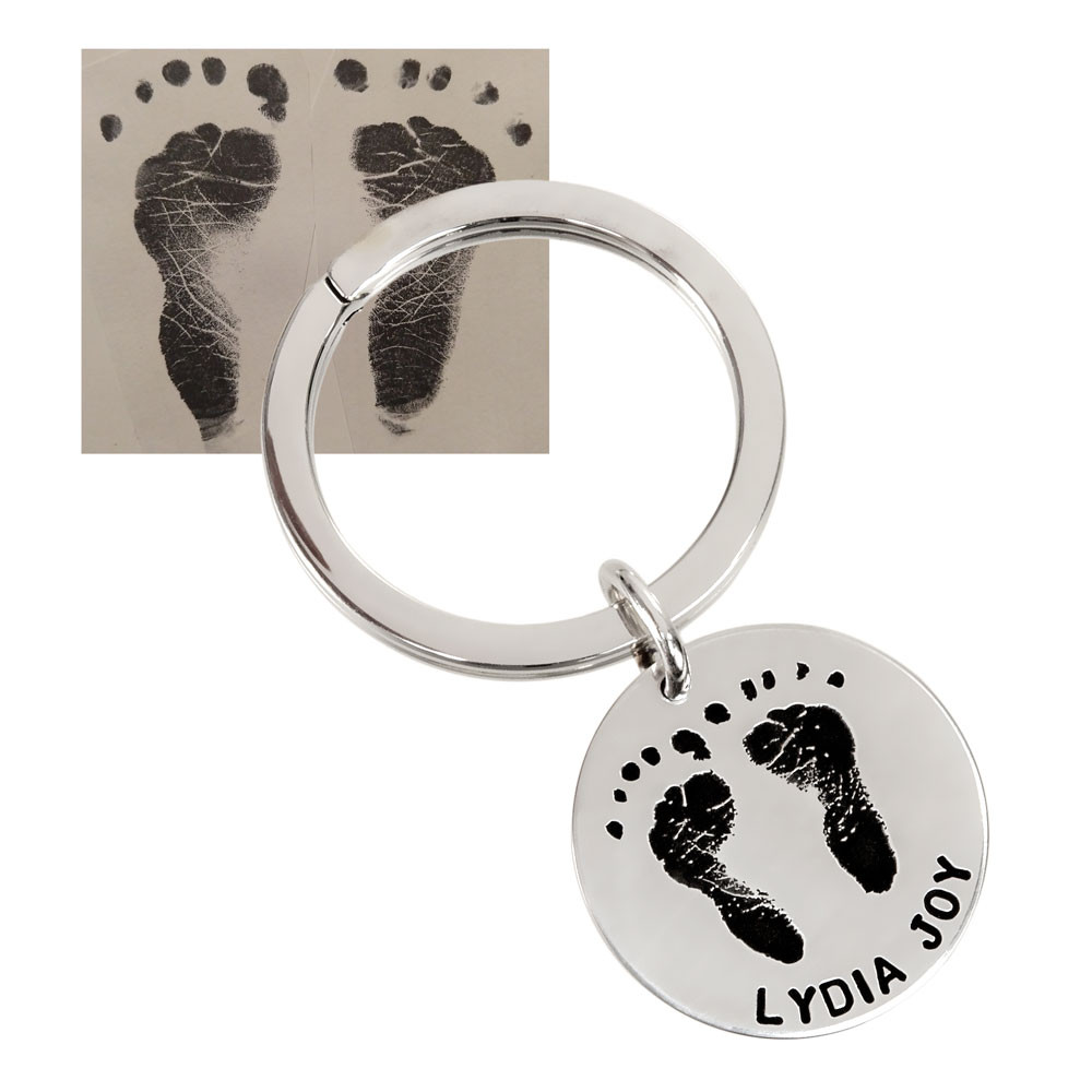 Child's foot prints on a custom sterling silver key ring, with a hand stamped message, shown with original footprints used to create it, close up on white