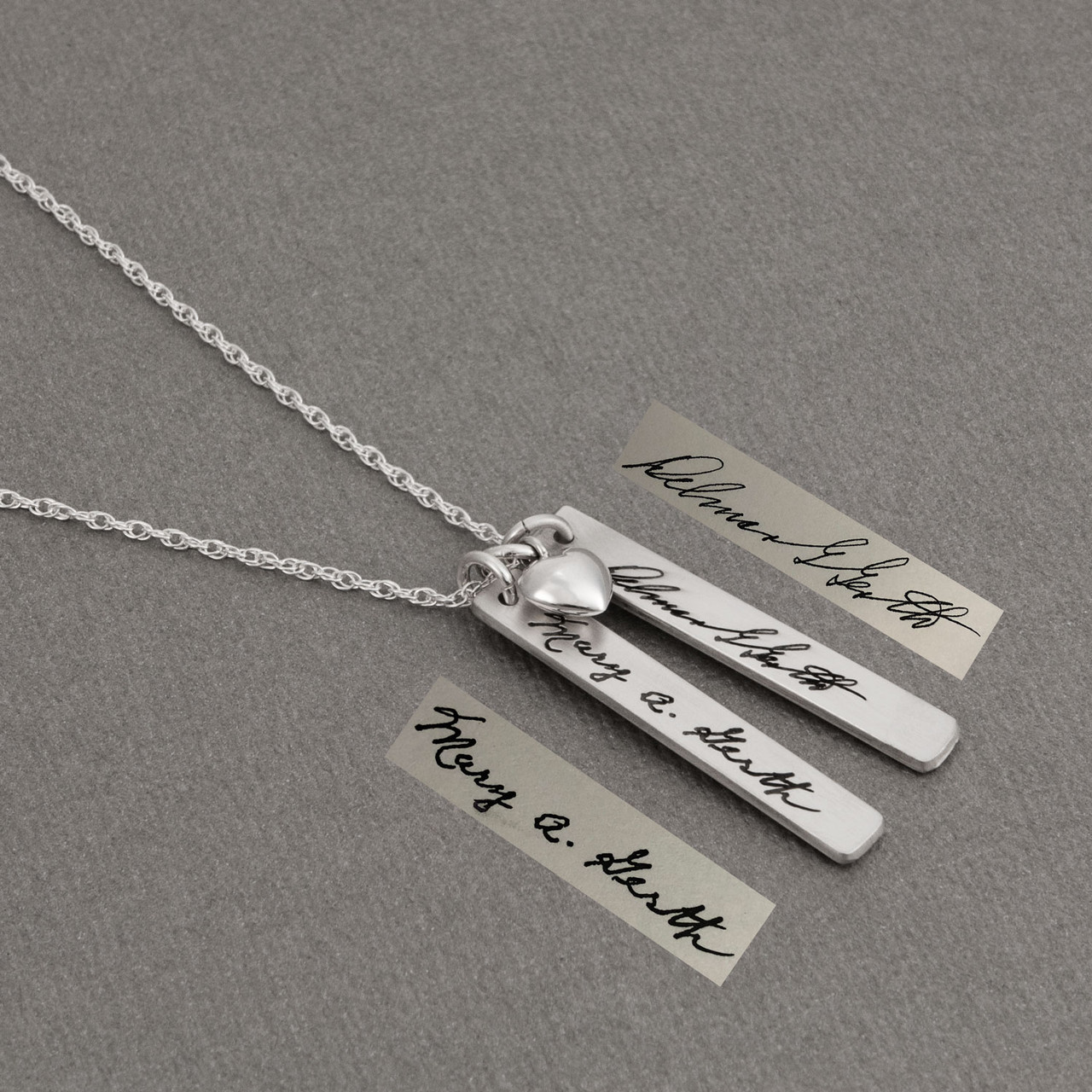 Custom Handwriting Tag in sterling silver, with actual handwriting, on gray background, shown with original handwriting