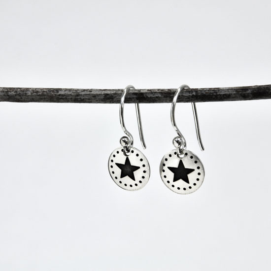 Dotted Star hand stamped Earrings shown hanging from a twig