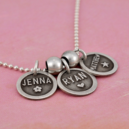 Silver Etched Name Disc Necklace personalized with kids names, shown close up from the side