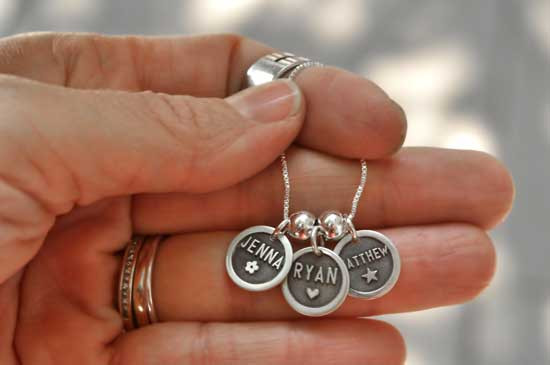 Silver Etched Name Disc Necklace personalized with kids names, shown in model hand