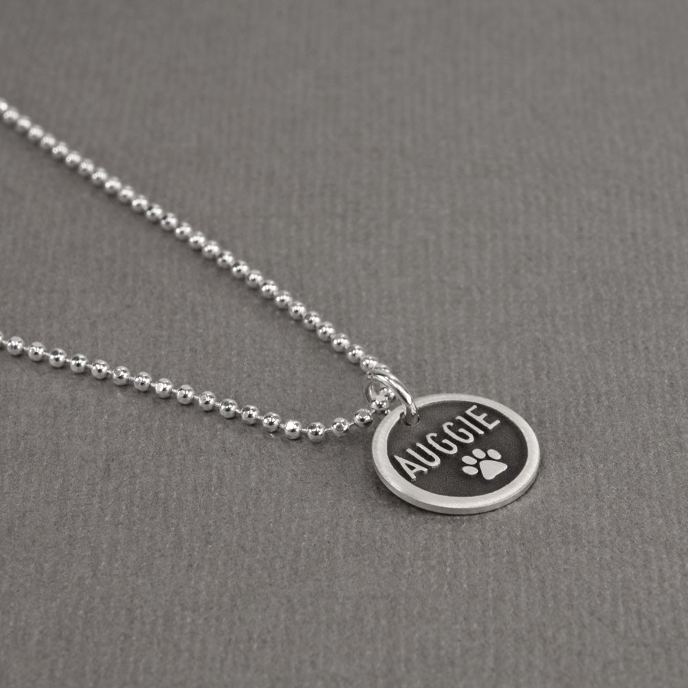Custom Silver Etched Paw Disc Necklace, with dog's name, shown from the side
