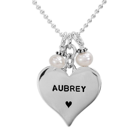 Close up view of Sterling silver heart stamped with a name on a silver chain with two pearls