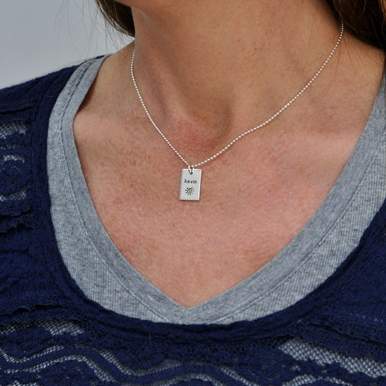 Personalized Funky Rectangle silver Necklace, hand stamped with kids' names, shown on a model