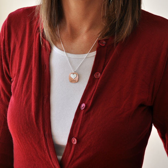 Hand stamped Fused Heart and Copper Necklace with silver heart, shown close up on white, shown on a model