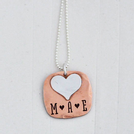 Hand stamped Fused Heart and Copper Necklace with silver heart, shown close up on white, with stamping MAE