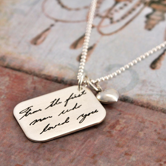 Handwritten note on a silver pendant