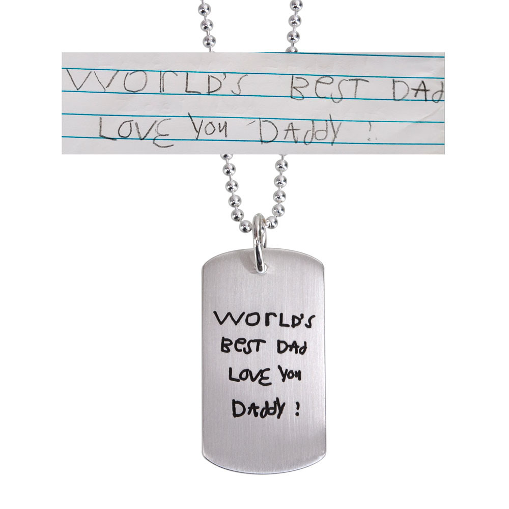 Custom silver dog tag necklace with child's handwriting, with the original handwritten note used to create it, shown on white