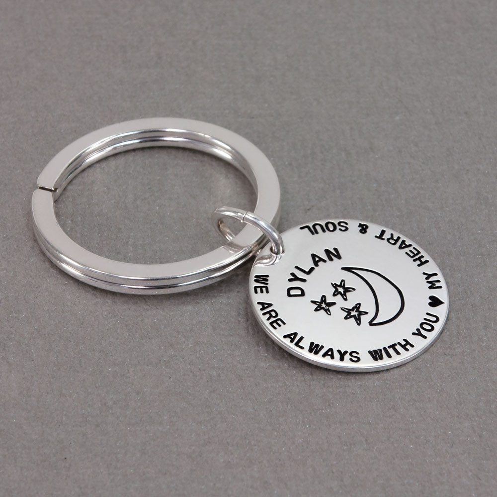 Custom hand stamped silver key chain for kid with parents' note, shown from the side