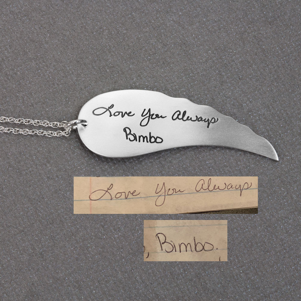 Large Handwriting Memorial Charm Angel Wing in silver, with a silver puffed heart, shown close up, with the original handwriting used to create it