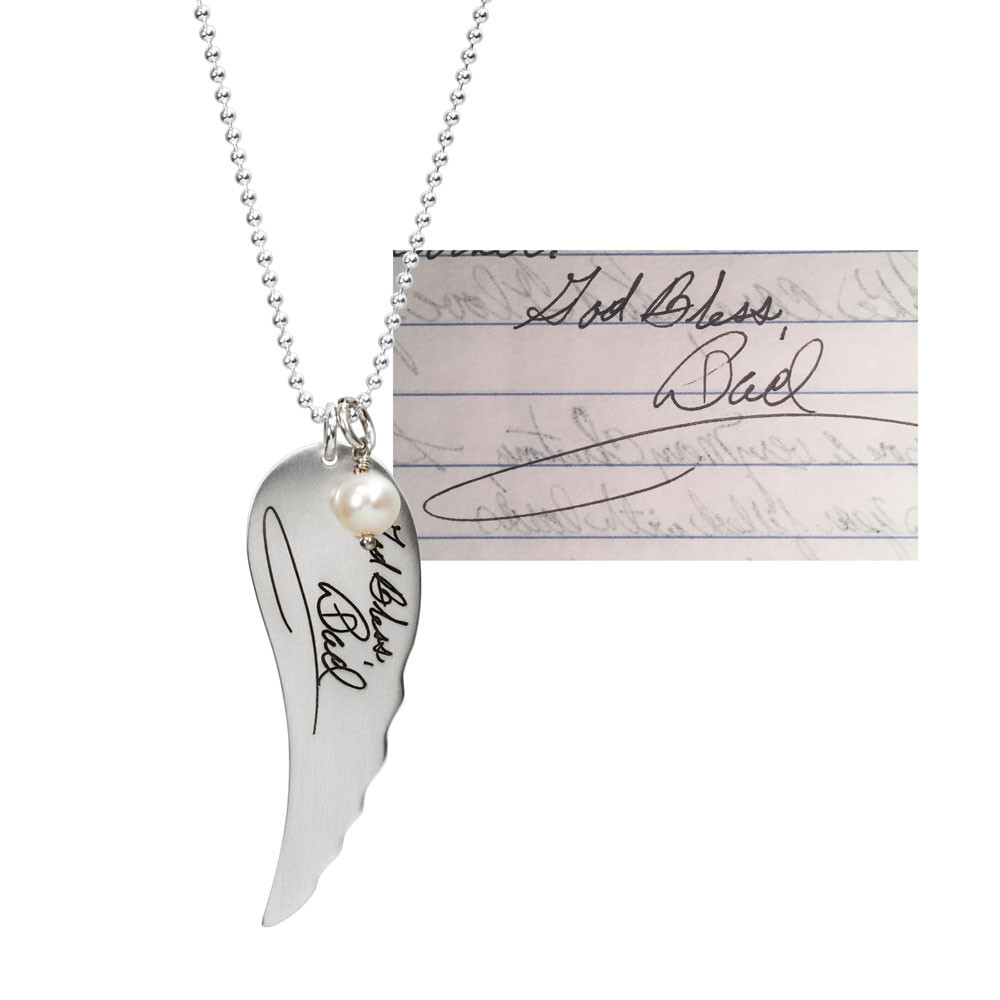 Large Handwriting Memorial Charm Angel Wing in silver, with a pearl, shown close up on white, with the original handwriting used to create it