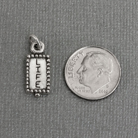 Sterling silver charm stamped with word life and image of flower on back, shown next to dime